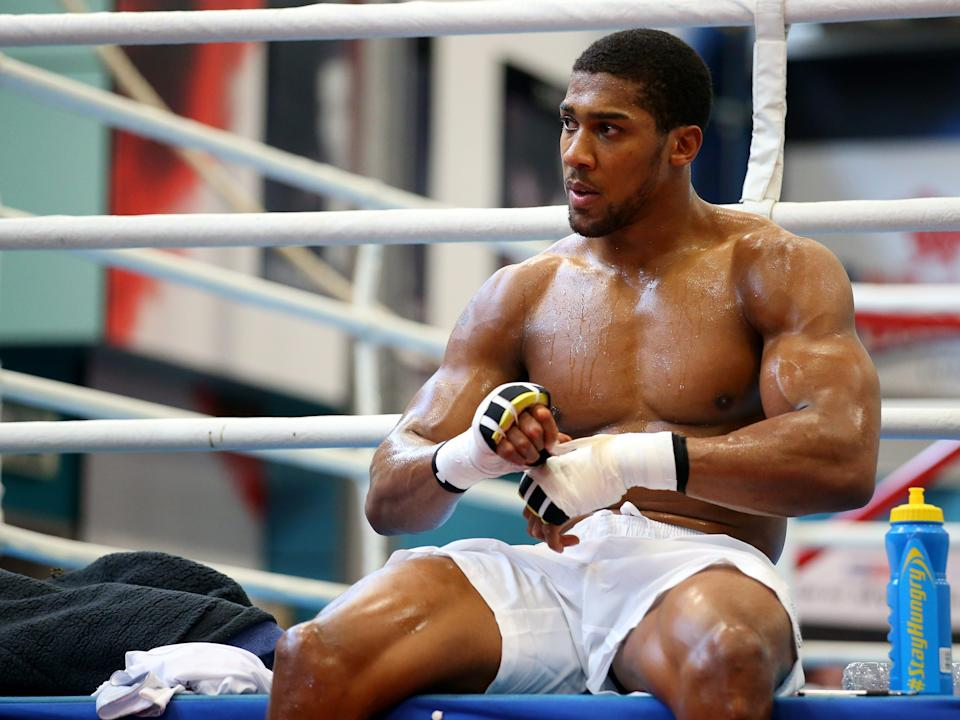 Anthony Joshua sitting on the edge of a boxing ring wrapping up his hands.