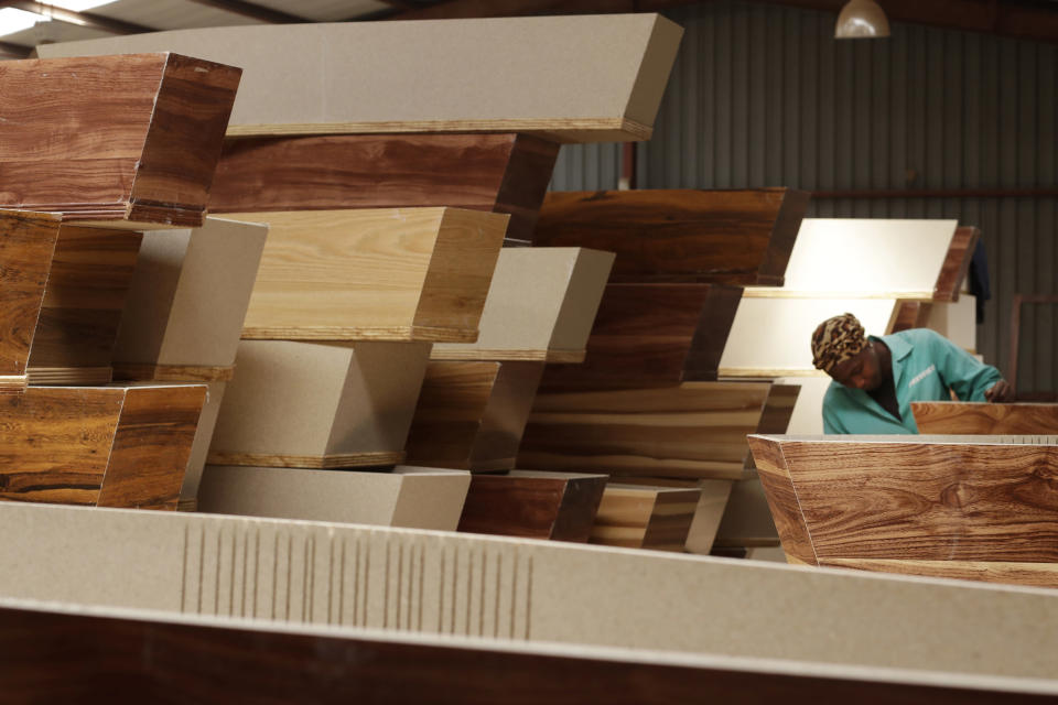 "A worker carries out her duties among stacked coffins at Enzo Wood Designs, in Johannesburg, Wednesday, Sept. 30. 2020. Casey Pillay, a coffin-maker in South Africa, watched the coronavirus pandemic turn his business upside down. For Pillay, the need for coffins rose and fell as South Africa's lockdown levels changed, but overall, he said, ""business went down."" As the world surpasses 1 million deaths, Africa is bracing for a likely second wave of infections. (AP Photo/Themba Hadebe)"