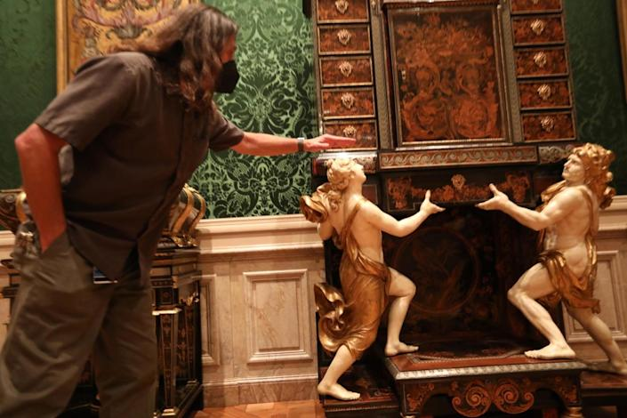 A preparator stands in front of cabinet supported by decorative cherubs.