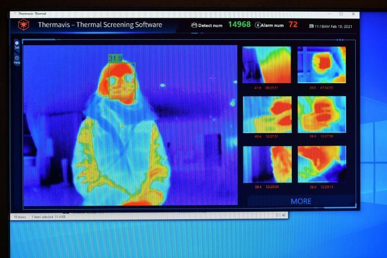 A thermal imaging camera are displayed on a screen as a person waits at the reception desk at the St Giles Hotel near Heathrow Airport in west London, in an example of technology being used to screen for Covid-19 symptoms