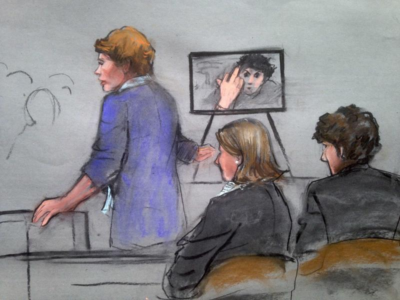 """Assistant U.S. Attorney Nadine Pellegrini (standing) speaks during the sentencing phase of the murder trial of Dzhokhar Tsarnaev, as Tsarnaev is seen gesturing in a photograph, in a courtroom sketch in Boston April 21, 2015. The Boston Marathon bombing was the """"essence of terror,""""  Pellegrini said on Tuesday as the government began making its case that convicted bomber Tsarnaev should be sentenced to death for the 2013 attack and its aftermath.  REUTERS/Jane Collins"""