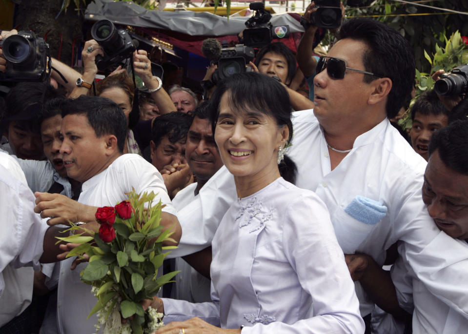 FILE - In this April 2, 2012, file photo, Myanmar pro-democracy leader Aung San Suu Kyi, center, arrives at the headquarters of her National League for Democracy party, in Yangon, Myanmar. Myanmar's military has taken control of the country under a one-year state of emergency and reports say State Counsellor Aung San Suu Kyi and other government leaders have been detained. (AP Photo/Khin Maung Win, File)