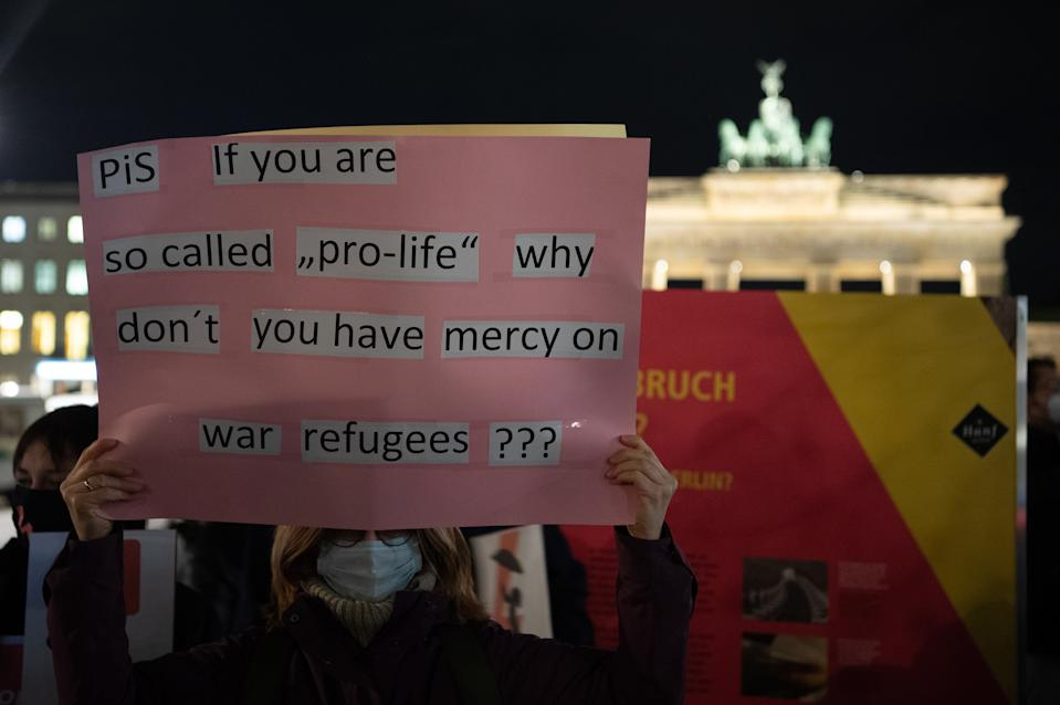 """29 October 2020, Berlin: A woman holds a poster in front of the Brandenburg Gate saying """"PiS if you are so-called """"pro-life"""" why don't you have mercy on war refugees? (PiS if you are """"for life"""" why don't you have mercy on refugees?). Demonstrators protested here against a tightening of the abortion ban in Poland. Photo: Paul Zinken/dpa-Zentralbild/dpa (Photo by Paul Zinken/picture alliance via Getty Images)"""