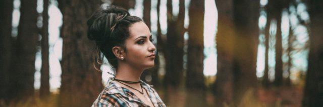 woman in a forest leaning against a tree with a straight face, hair in a bun and makeup on