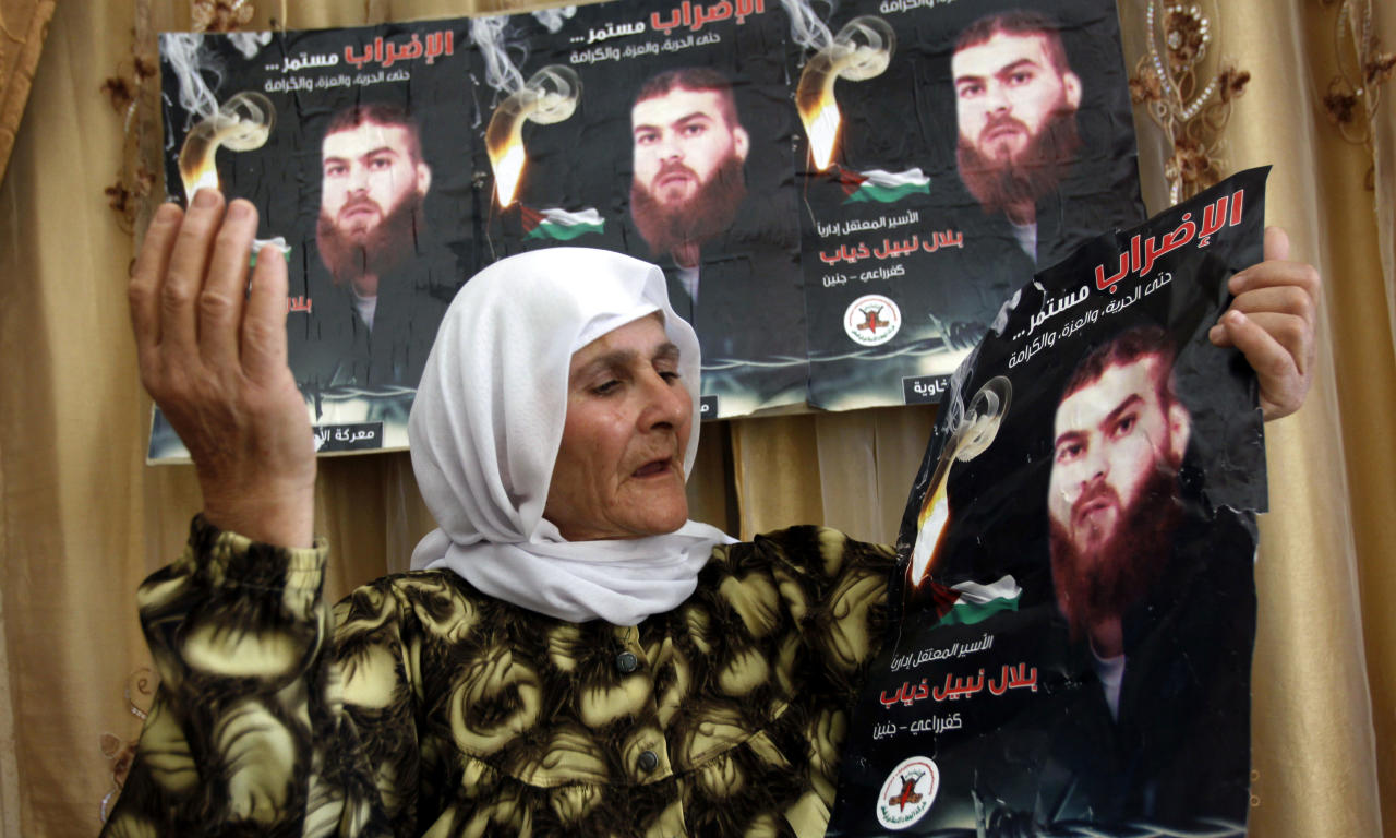 "In this Sunday, May 6, 2012 photo, Palestinian Missadeh Diab, 65, holds posters of her son Bilal, who has been on a hunger strike since Feb. 28, 2012 in an Israeli prison, at her home in the West Bank village of Kufr Rai near Jenin. According to Israel's Prison Service at least one-third of the 4,600 Palestinian prisoners in Israel began a collective hunger strike in mid-April 2012. The Arabic on the posters reads ""the strike will continue, Bilal Nabil Diab."" (AP Photo/Mohammed Ballas)"