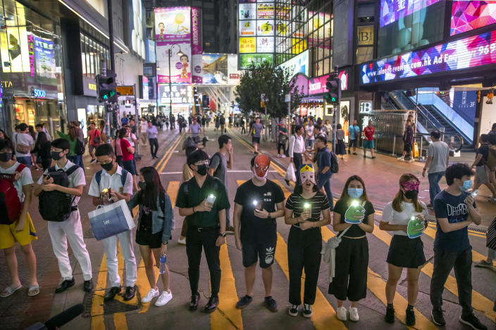 Protestors wearing masks stand along a commercial shopping street in Hong Kong, Friday, Oct. 18, 2019. Hong Kong pro-democracy protesters are donning cartoon and superhero masks as they formed a human chain across the semiautonomous Chinese city, in defiance of a government ban on face coverings. (AP Photo/Mark Schiefelbein)