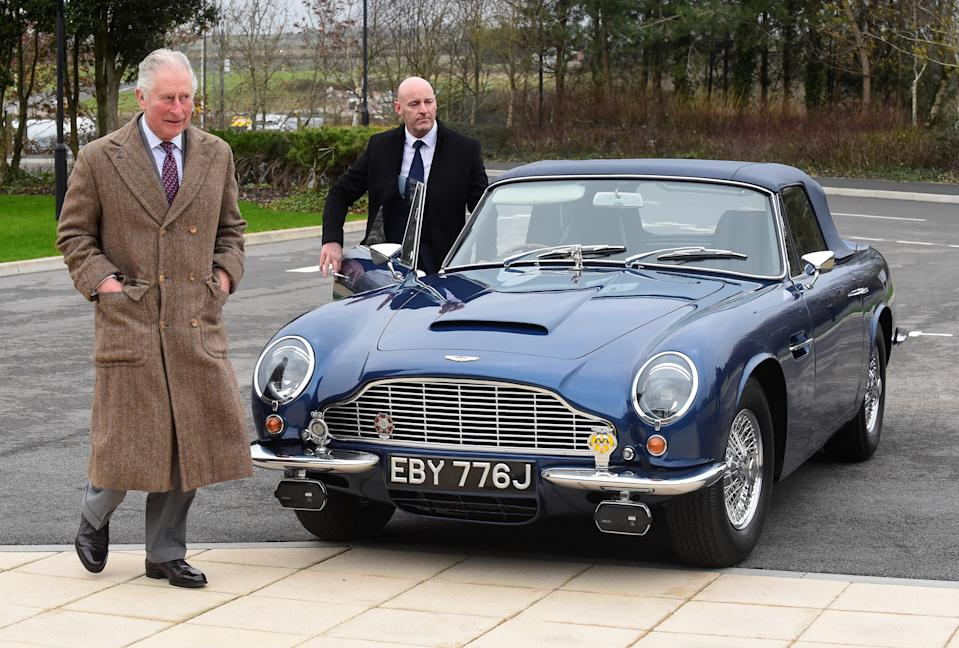 The Prince of Wales with his Aston Martin DB6 as he arrives for a visit to the Aston Martin Lagonda factory at St Athan in Barry, Wales.