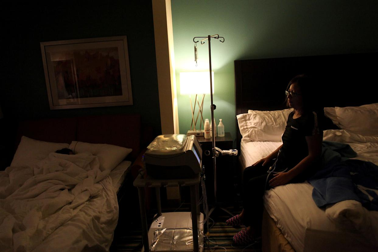 Waleska Rivera, 42, looks at her sleeping 9-year-old son as she undergoes her dialysis treatment in a hotel room in Orlando, Florida, on Dec. 7, 2017. (Photo: Alvin Baez/Reuters)