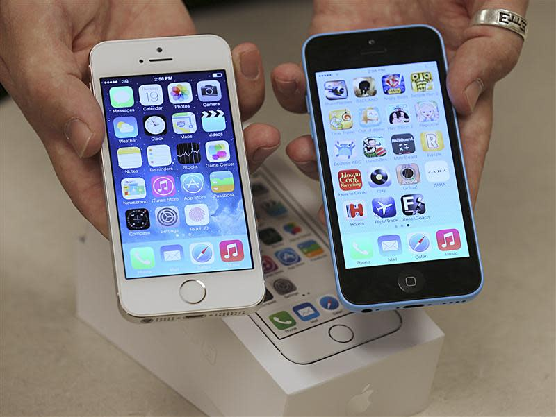 An employee shows the the front of a new Apple iPhone 5C and iPhone 5 S at a Verizon store in Orem, Utah