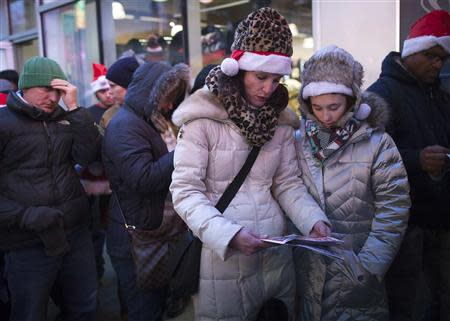 """People line up and read the sales flyer outside a Toys""""R""""Us store in Times Square before their Black Friday Sale in New York November 28, 2013. REUTERS/Carlo Allegri"""