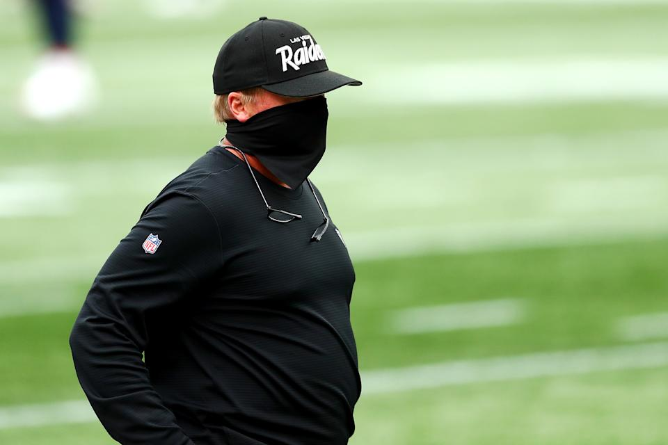 Jon Gruden stands on the field before the game against the Patriots with a full mask covering his face.
