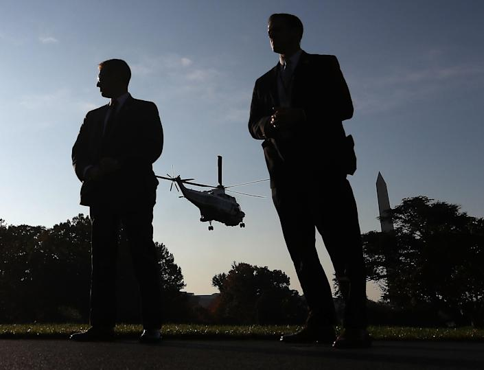 <p>Two members of the US Secret Service stand guard as Marine One carrying US President Donald Trump takes off from the south lawn of the White House on November 3, 2017 in Washington. (Photo: Mark Wilson/Getty Images) </p>