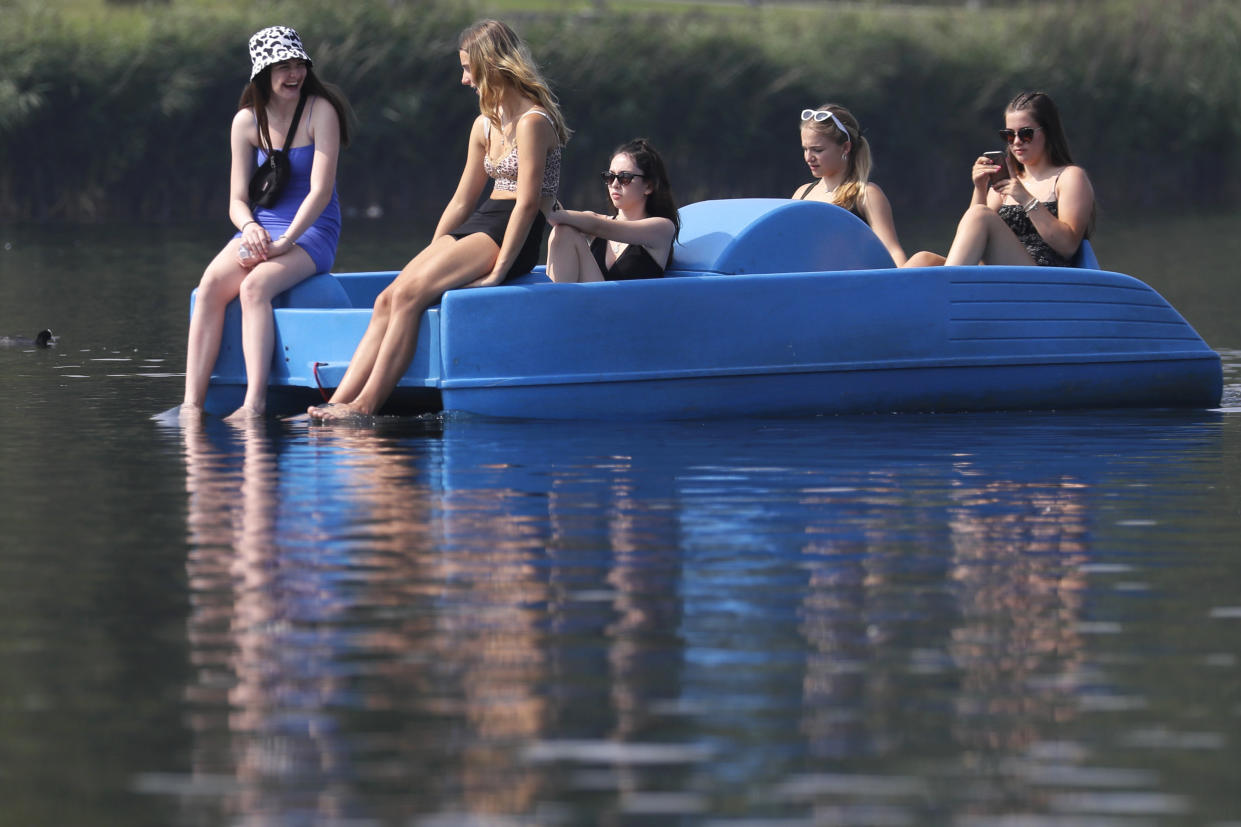 People relax in a pedal boat on The Serpentine in Hyde Park in London, Wednesday, Aug. 12, 2020. Thunderstorm warnings are still current for most of the UK on Wednesday, while high temperatures are forecast again for many parts of England. (AP Photo/Kirsty Wigglesworth)