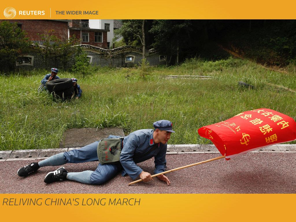 "A man in ""Red Army"" garb hits the pavement during a simulated attack during a re-staging of part of the Long March. The scene brings alive an extraordinary chapter in China's history that established the supremacy of Chairman Mao Zedong and the Communist Party. Deep in the mountains of Jinggangshan in the southeastern province of Jiangxi, a classroom of bank tellers participates in an ideological boot camp that plays into Chinese President Xi Jinping's drive to further consolidate his grip on power. REUTERS/Thomas Peter  SEARCH ""LONGMARCH PETER"" FOR THIS STORY. SEARCH ""WIDER IMAGE"" FOR ALL STORIES. TPX IMAGES OF THE DAY.  Matching text: CHINA-CONGRESS/LONGMARCH"
