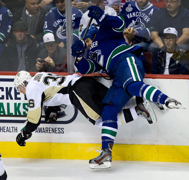 Vancouver Canucks' Tom Sestito, right, checks Pittsburgh Penguins' Jussi Jokinen, of Finland, during second period NHL hockey action in Vancouver, British Columbia, on Tuesday Jan. 7, 2014. (AP Photo/The Canadian Press, Darryl Dyck)