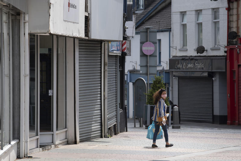 MERTHYR TYDFIL, UNITED KINGDOM - MAY 18: A woman wears a face mask and surgical gloves while carrying a bag and walking passed closed small businesses on High Street on May 18, 2020 in Merthyr Tydfil, United Kingdom. The British government has started easing the lockdown it imposed two months ago to curb the spread of Covid-19, abandoning its 'stay at home' slogan in favour of a message to 'be alert', but UK countries have varied in their approaches to relaxing quarantine measures. (Photo by Matthew Horwood/Getty Images)