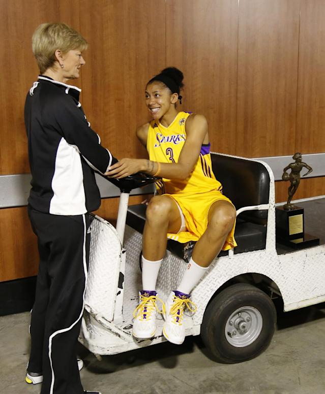 Los Angeles Sparks' forward Candace Parker, right, sits next to her WNBA MVP trophy on a cart as she talks with head coach Carol Ross outside the locker room before playing the Phoenix Mercury in the opener of their WNBA basketball Western Conference semifinal series on Thursday, Sept. 19, 2013, in Los Angeles. (AP Photo/Danny Moloshok)