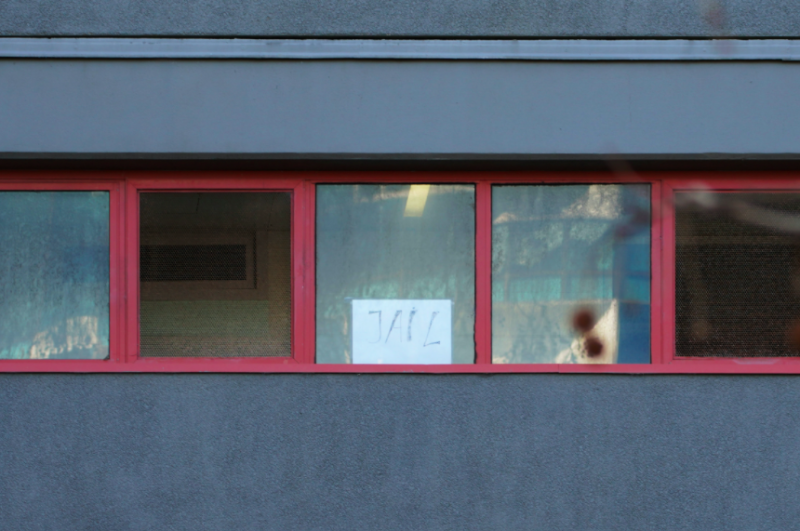 A resident places a 'jail' sign on their window as those inside are kept under police guard. (Reuters)