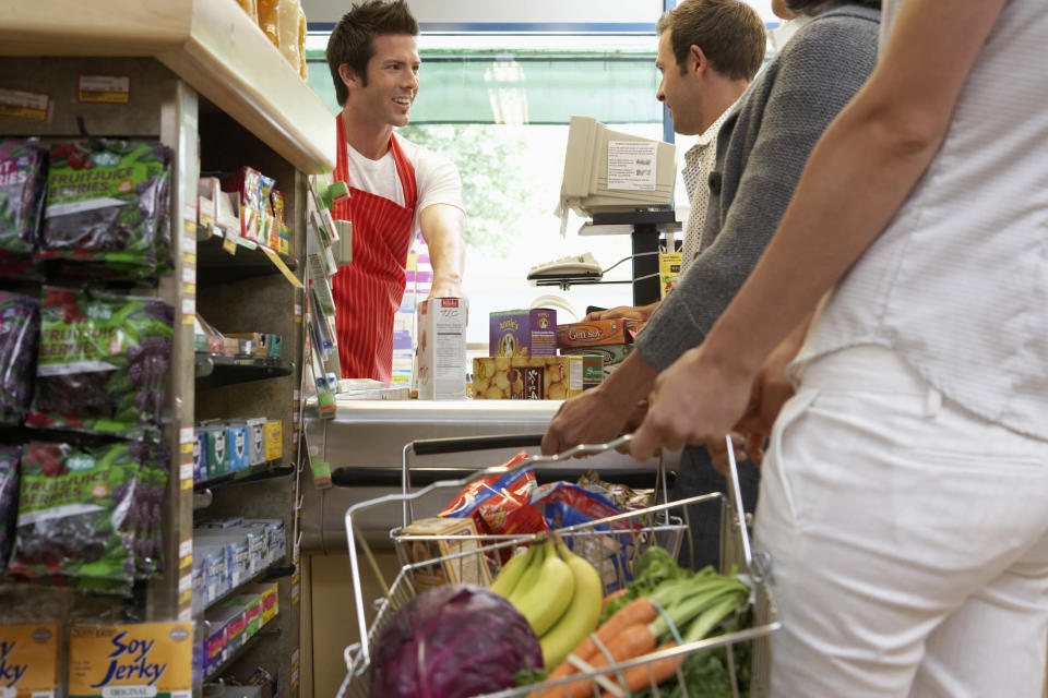A shopper in a supermarket waiting in line to pay with a basket of fruits and vegetables.