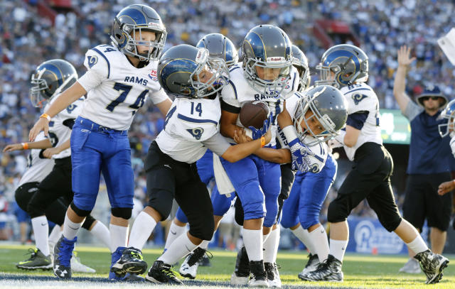 FILE- In this Aug 13, 2016, file photo, youngsters play in a pee-wee football game during halftime of a preseason NFL football game between the Los Angeles Rams and the Dallas Cowboys in Los Angeles. USA Football is piloting the sports first long-term development program in the hopes of growing the game and catching up to other sports around the world. The sports governing body has launched its Football Development Model. Six youth leagues will team up with USA Football in the hopes of attracting more young players and improving skills. The leagues will experiment with new ways to coach fundamentals in practice and different ways to play the game. (AP Photo/Ryan Kang, File)