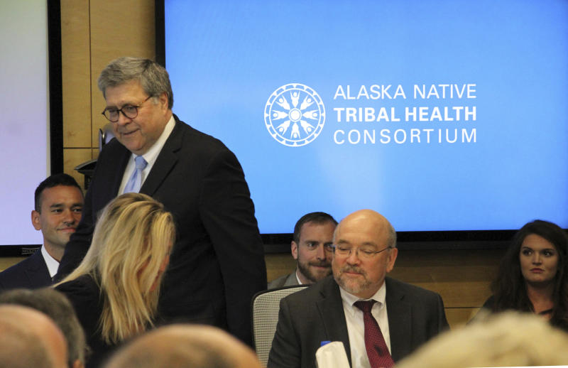 FILE - In this May 29, 2019 file photo U.S. Attorney General William Barr, standing, greets participants at a roundtable discussion at the Alaska Native Tribal Health Consortium in Anchorage, Alaska. Alaska Native villages are receiving almost $5 million from the U.S. Justice Department to combat numerous public safety problems, including no law enforcement presence in some communities. The announcement Tuesday, July 30, 2019, comes nearly two months after Barr met with tribal representatives during a visit to the state who detailed slow response times from authorities, violence against women and abuse of alcohol and drugs, including opioids. (AP Photo/Mark Thiessen, File)