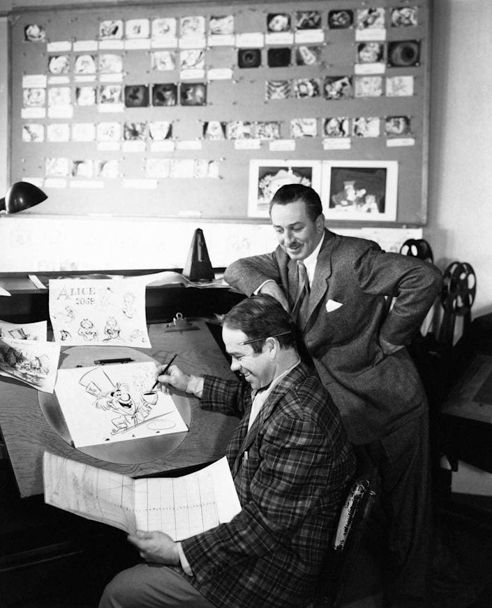 ALICE IN WONDERLAND, from left: animator Ward Kimball works on a drawing of The Mad Hatter as producer Walt Disney looks on - Alamy