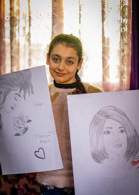 Syrian refugee, Rahma, 11, currently living in a displacement camp in Jordan, display their artwork ahead of their collaborative exhibit at Kings Playhouse in Georgetown, PEI (CNW Group/World Vision Canada)