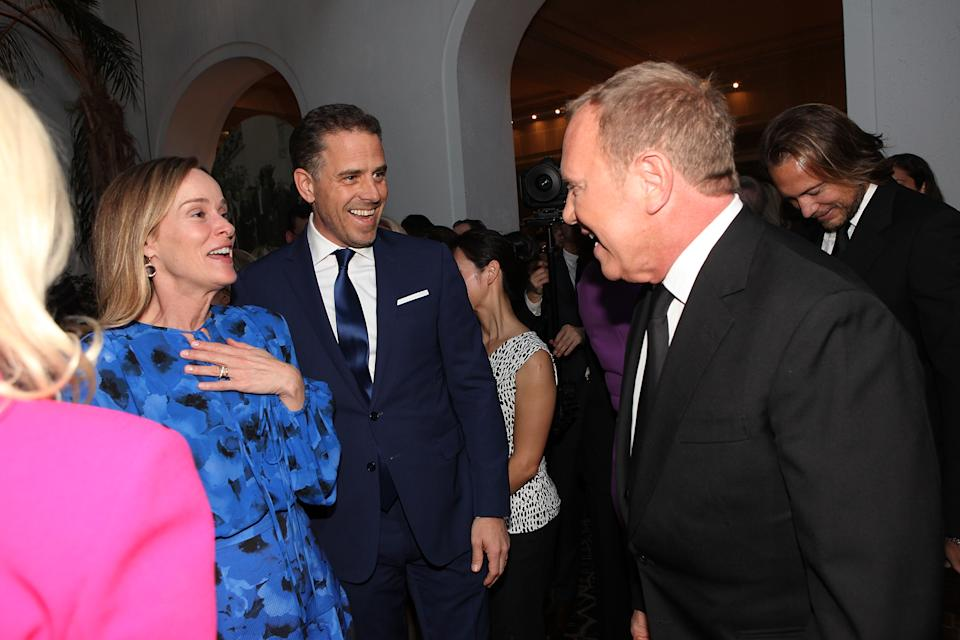Kathleen Biden, Hunter Biden and designer Michael Kors smile while speaking to each other in a room with others