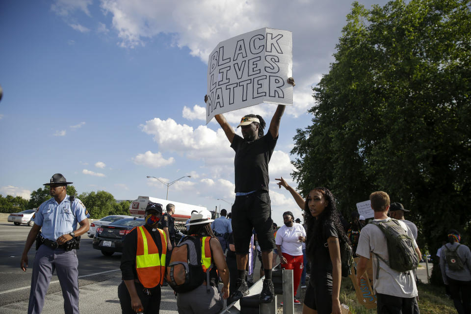 A man holds up a Black Lives Matters poster by the interstate near the Wendy's restaurant, in Atlanta, Saturday, June 13, 2020, where Rayshard Brooks was fatally shot by police late Friday during a struggle following a field sobriety test. Authorities said the slain man had grabbed an officer's Taser, but was running away when he was shot. (AP Photo/Brynn Anderson)