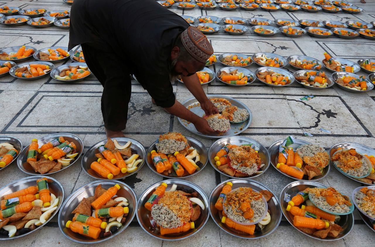 A man arranges food plates for people to break fast at a mosque duringa Muslim holy month of Ramadan in Karachi, Pakistan May 28, 2017. REUTERS/Akhtar Soomro