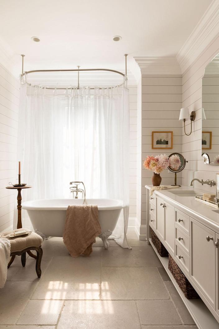 The serene bathroom features a freestanding tub by Cheviot, Riobel faucet, and wall scones courtesy of Chairish.