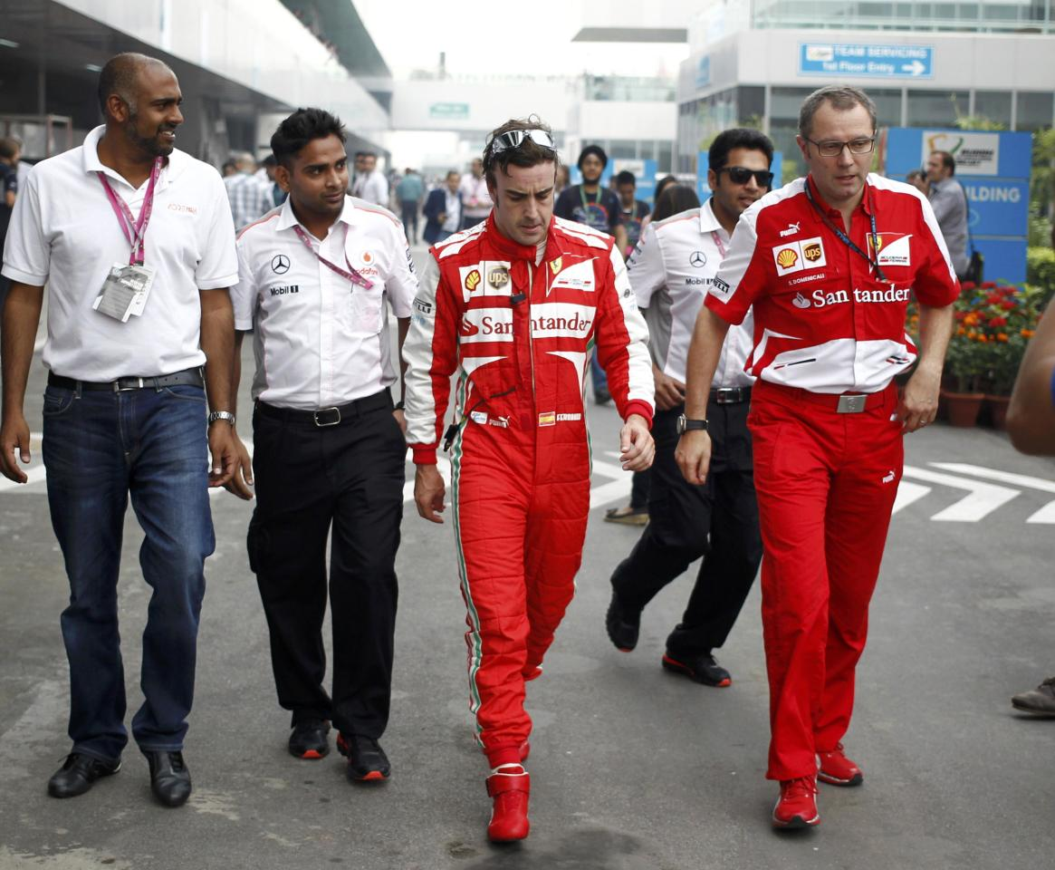 Ferrari Formula One driver Fernando Alonso of Spain (C) walks with Team Principal Stefano Domenicali (R) during the Indian F1 Grand Prix at the Buddh International Circuit in Greater Noida, on the outskirts of New Delhi, October 25, 2013. REUTERS/Anindito Mukherjee (INDIA - Tags: SPORT MOTORSPORT F1)