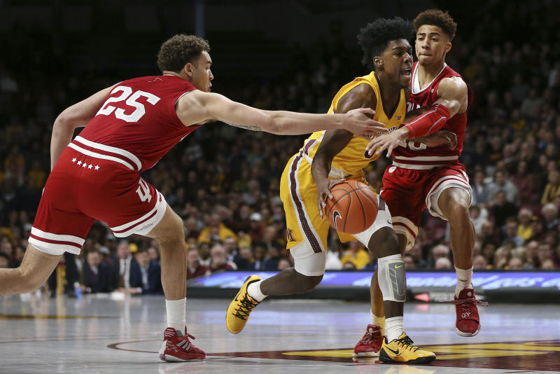 Minnesota's Marcus Carr maneuvers the ball through the defense of Indiana's Race Thompson, left, and Rob Phinisee during the first half of an NCAA college basketball game Wednesday, Feb. 19, 2020, in Minneapolis. (AP Photo/Stacy Bengs)
