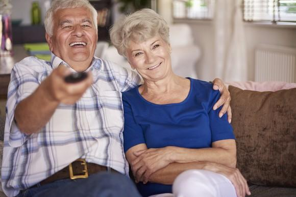 A smiling senior couple sitting side by side on a sofa, with the man holding a TV remote in one hand and his other arm around the woman's shoulders.
