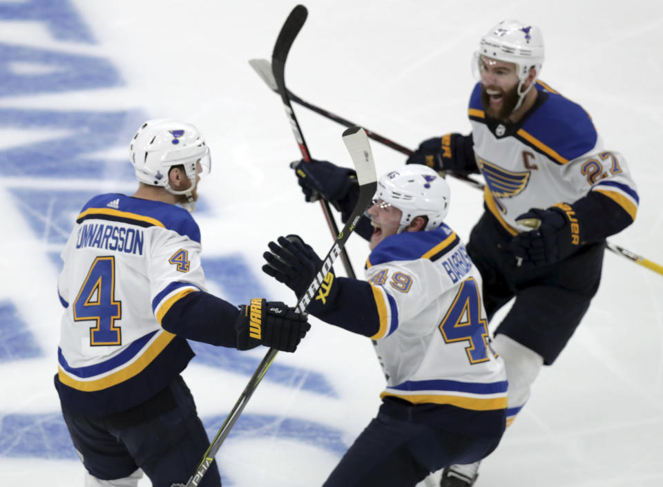 CORRECTS SOURCE AND PHOTOGRAPHER'S NAME - St. Louis Blues' Carl Gunnarsson (4), of Sweden, is congratulated by Ivan Barbashev (49), of Russia and Alex Pietrangelo, right, after he scored the winning goal against the Boston Bruins during the first overtime period in Game 2 of the NHL hockey Stanley Cup Final, Wednesday, May 29, 2019, in Boston. (AP Photo/Charles Krupa)