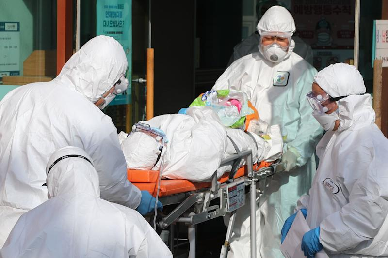 Medical workers wearing protective gear transfer a suspected coronavirus patient to another hospital from Daenam Hospital: YONHAP/AFP via Getty Images