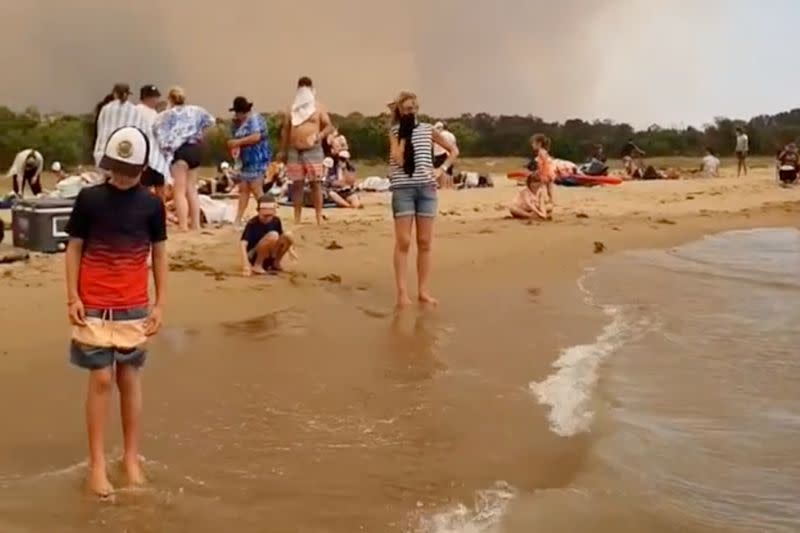 People at the beach evacuate from the bushfires at Batemans Bay