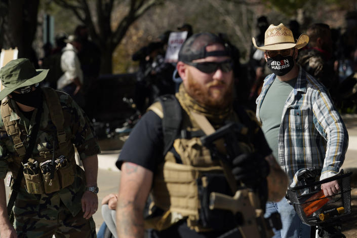 Mark Hogendobler, right, watches as armed demonstrators gather outside the locked gates of the Texas State Capitol, Sunday, Jan. 17, 2021, in Austin, Texas. (AP Photo/Eric Gay)