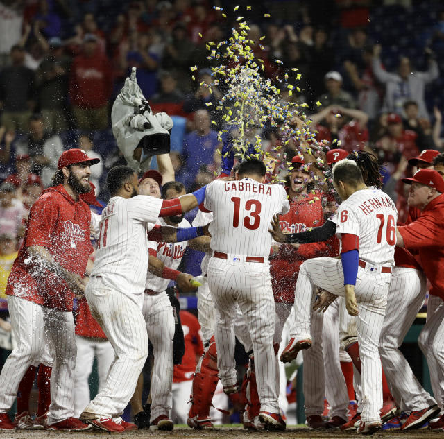 Philadelphia Phillies' Asdrubal Cabrera (13) is mobbed by his teammates after hitting the game-winning home run off Chicago Cubs relief pitcher Steve Cishek during the 10th inning of a baseball game Friday, Aug. 31, 2018, in Philadelphia. Philadelphia won 2-1. (AP Photo/Matt Slocum)