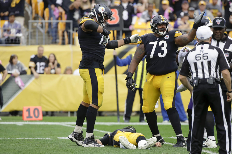 Pittsburgh Steelers offensive guards Ramon Foster (73) and Alejandro Villanueva (78) call for help after quarterback Mason Rudolph (2) was injured in the second half of an NFL football game against the Baltimore Ravens, Sunday, Oct. 6, 2019, in Pittsburgh. (AP Photo/Don Wright)