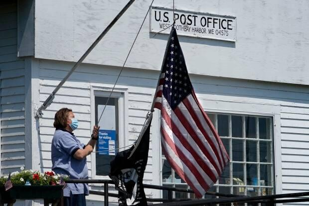 An employee raises the American flag outside a branch of the U.S. Post Office, Wednesday, July 7, 2021, in West Boothbay Harbor, Maine. Many post offices still require the use of face coverings due to COVID-19. (Robert F. Bukaty/The Associated Press - image credit)