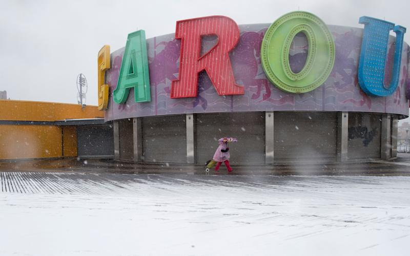A woman pulls a cart as she walks past the Carousel during a snow storm on the Coney Island boardwalk on Friday - Credit: AP