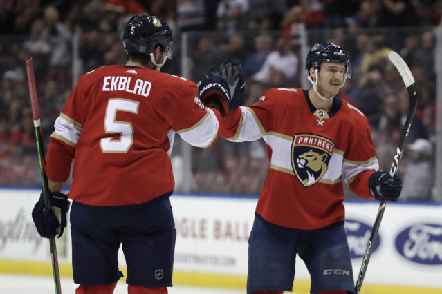 Florida Panthers center Jonathan Huberdeau, right, celebrates with defenseman Aaron Ekblad (5) after scoring a goal during the first period of an NHL hockey game against the Minnesota Wild, Tuesday, Dec. 3, 2019, in Sunrise, Fla. (AP Photo/Lynne Sladky)
