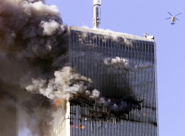 The World Trade Center in New York City burns as a police helicopter flies nearby early September 11, 2001. (Jeff Christensen/Reuters)