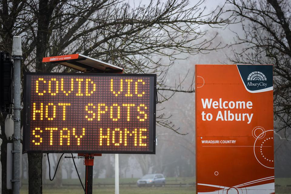 A sign is displayed regarding coronavirus restrictions in the NSW, Victoria border town of Albury. Source: Getty
