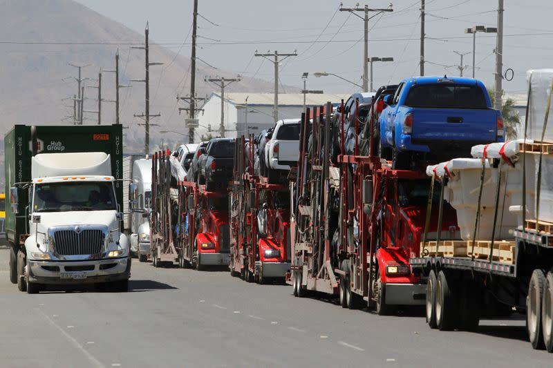 Carrier trailers transport Toyota vehicles for delivery while queuing at the border for customs control to cross into the U.S., at the Otay border crossing in Tijuana
