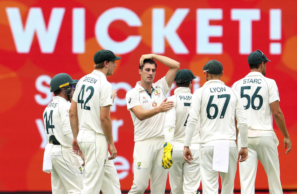 Australia's Pat Cummins, centre, celebrates with teammates after dismissing India's Rohit Sharma during play on the final day of the fourth cricket test between India and Australia at the Gabba, Brisbane, Australia, Tuesday, Jan. 19, 2021. (AP Photo/Tertius Pickard)