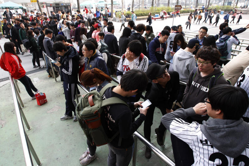People line up to buy tickets for a pro-baseball game at the Jamsil Baseball Stadium in Seoul, South Korea, Friday, April 5, 2013. Outsiders might hear the opening notes of a war in the deluge of threats and provocations from North Korea, but to South Koreans it is a familiar song. Foreigners unused to North Korean rumblings have canceled trips to the Korean Peninsula. But to get South Koreans' attention, Pyongyang must compete with the economy, celebrity scandals, baseball games and cherry blossoms. (AP Photo/Ahn Young-joon)