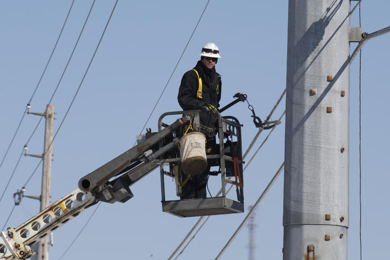 A communications lineman works on installing fiber optic lines on Friday, March 6, 2015 in Cranberry, Pa. (AP Photo/Keith Srakocic)