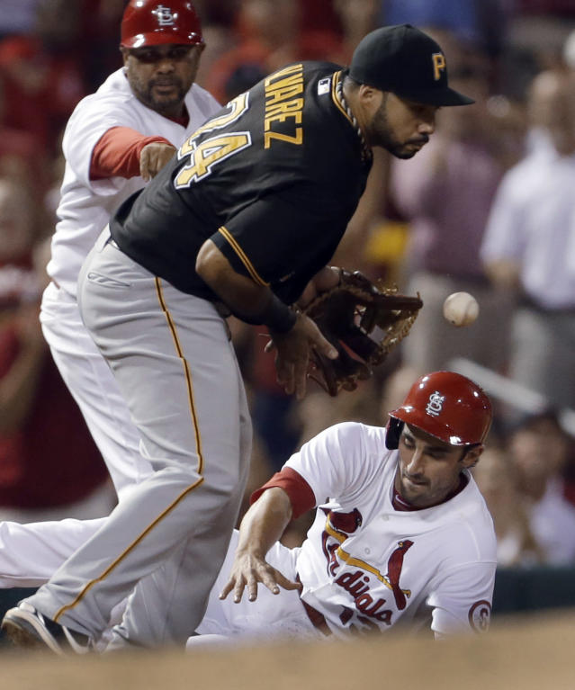 St. Louis Cardinals' Matt Carpenter, bottom, is safe at third for a triple as Pittsburgh Pirates third baseman Pedro Alvarez (24) handles the throw during the third inning of a baseball game Friday, Sept. 6, 2013, in St. Louis. (AP Photo/Jeff Roberson)
